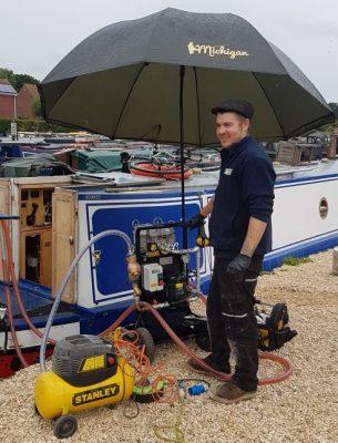marine engineer working on a narrowboat in the rain